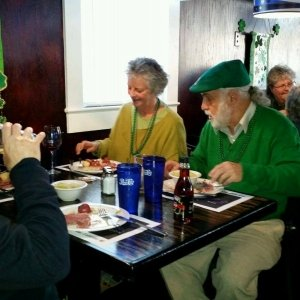 Man in Green Eating Dinner with Friends